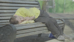 Poverty. A tramp asleep on a bench in the park Footage