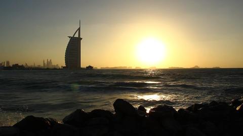 Burj Al Arab black silhouette, surf waves, sunset time over Persian Gulf Footage