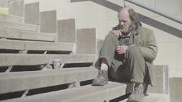 A beggar homeless man is sitting on the steps Footage