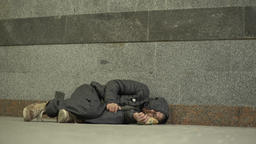 Poverty. The homeless man sleeps on the floor of an underpass Footage