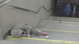 Poverty. The homeless man sleeps on the steps of the metro Footage