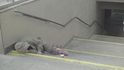Vagrancy. . The homeless man sleeps on the steps of the metro Footage
