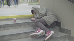Poverty. The homeless man sleeps on the street on the steps Footage