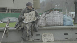 "Homeless man on the street with a poster ""Work for food"" Live Action"