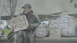 "Homeless man on the street with a poster ""Need food"" Live Action"