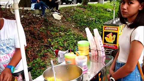 A street food vendors serves sweet corn to a customer Filmmaterial