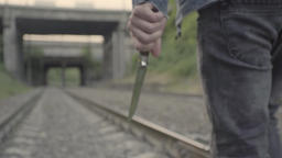 Man killer maniac comes with a knife in his hand by rail Footage