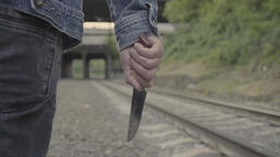 The killer comes with a knife in his hand by rail Footage