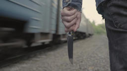 A maniac killer with a knife is walking next to the traveling train. Close-up Footage