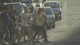 Many people in the city cross the road on the pedestrian crossing. Crowd Footage