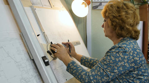 Side View Woman Draws Plan on Drawing Board under Lamp Light Live Action