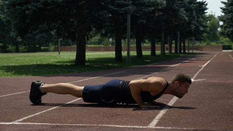 Athletic sportsman doing pushups on running track Footage