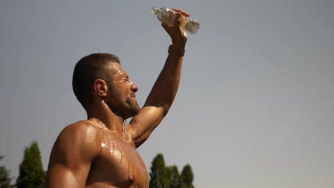 Thirsty sweated guy pours water over his head and body to cool down in hot summe Footage