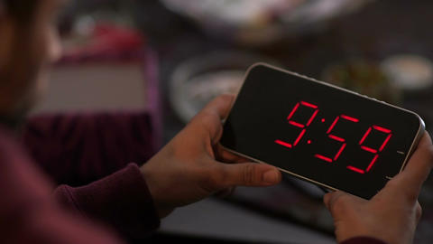 Cinemagraph of man holding a digital clock and looking at the time passes and go Footage
