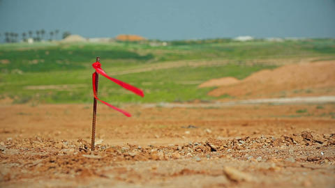 Cinemagraph of metal survey peg with red flag on construction site Archivo
