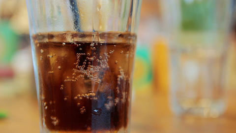 Cinemagraph of bubble bubbling in glass with cola and ice on a table Footage