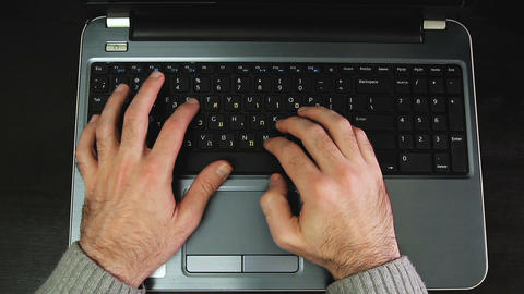 Cinemagraph of man typing on a keyboard with letters in Hebrew and English GIF