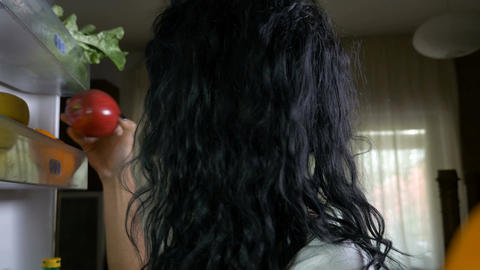 Young woman on diet opening refrigerator and looking to fresh fruits Live Action