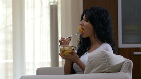 Young woman sitting on a couch watching TV and eating fruit salad having healthy Live Action