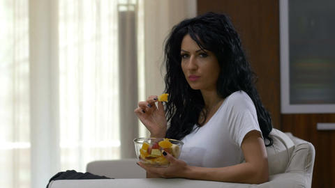 Young woman sitting on couch enjoying her fruit salad eating healthy food and ha Live Action