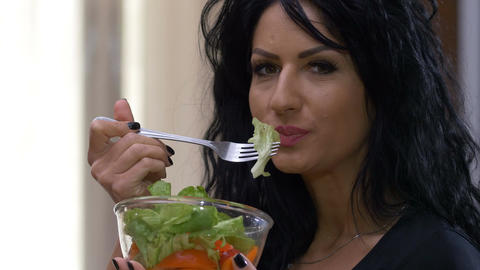 Closeup fit woman really enjoying her fresh bowl of organic vegetables salad Footage