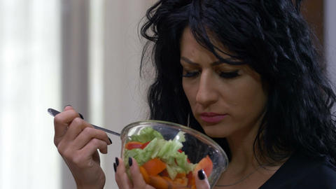 Attractive unhappy woman dislike eating vegetarian healthy food Live Action