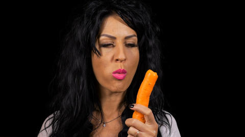 Healthy beautiful woman tasting and eating a carrot Footage