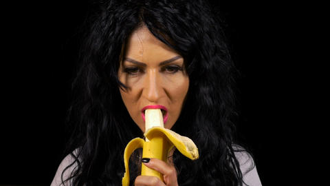 Young woman eating a banana healthy lifestyle with black background Live Action