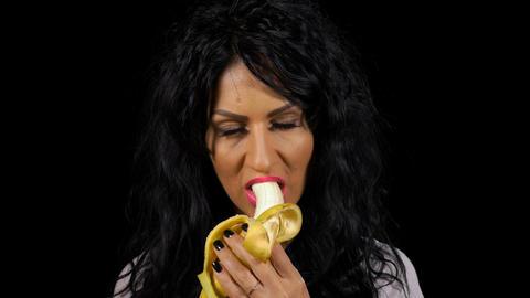 Smiling woman peeling and eating banana Live Action