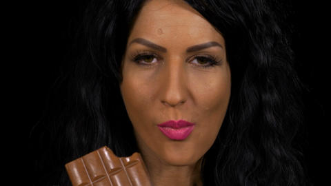 Young woman biting on a piece of dark chocolate closeup Footage