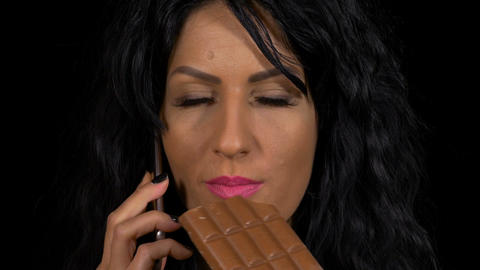 Closeup of attractive female chatting at smartphone while eating a chocolate Live Action