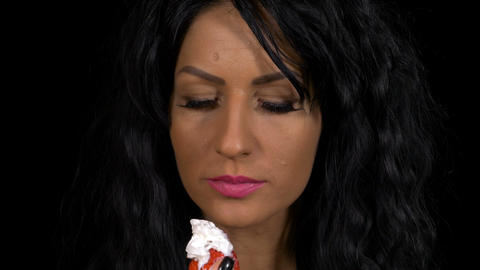 Closeup of gourmet woman eating a strawberry with whipped cream topping Footage