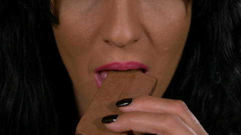 Closeup of young woman addicted to sweets eating a brown chocolate candy bar slo Footage