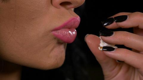 Closeup of seductive woman eating popcorn Live Action