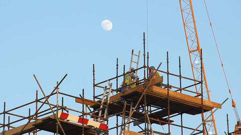 Workers at top of falsework, low angle telephoto shot, evening time Footage
