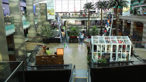 Modern Arabic mall interior, people move down on escalator, open atrium view Footage
