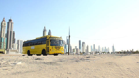 Yellow school bus stand still at deserted vacant lot, against modern city towers Footage