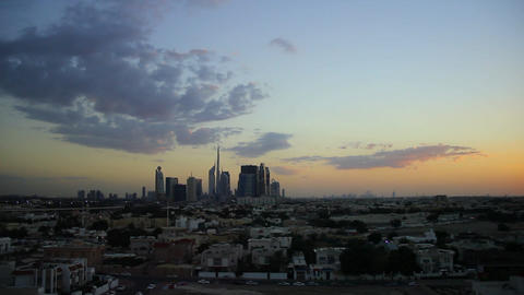 Afterglow to darkness sky time lapse. Light dark clouds over Dubai skyline Live Action
