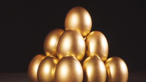 Golden eggs. Gold eggs on black background ビデオ