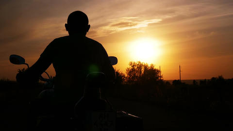 The biker turns to the right at sunset and leavest Filmmaterial
