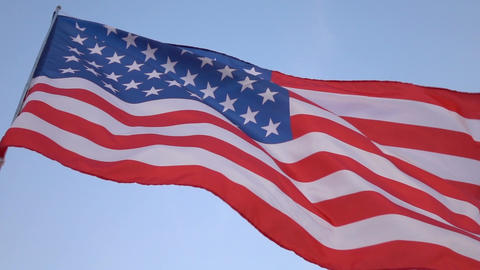 American flag in the wind on blue sky, slow motion Image