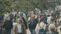 Crowded street. A crowd of people is walking down the street. Slow motion Footage