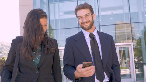 Two attractive contemporary businesspeople walking and looking up from a cell Footage
