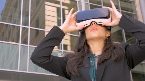 Sexy young female corporate executive in awe holding VR headset experiencing 360 Live Action