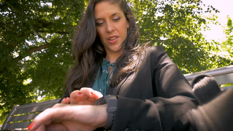 Smiling happy woman in her 30s using smart watch app technology in park slow Footage
