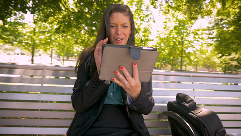Attractive woman in business clothing using digital tablet to video chat Footage