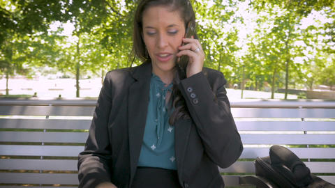 Attractive millennial businesswoman talking on smart phone while working with Footage