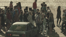 A crowd of people cross the street on a pedestrian crossing. Slow motion Footage