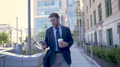Successful millennial businessman walking away from modern glass office building Footage