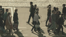 Crowd of people cross the street on a pedestrian crossing. Slow motion Footage